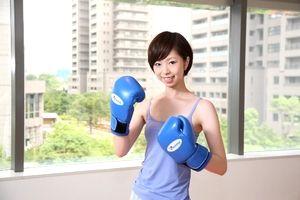 フィットネスジムでボクシングする若いショートカットの女性。