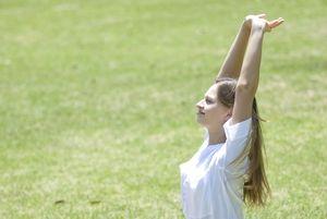 大草原の中で背伸びをする若い女性。