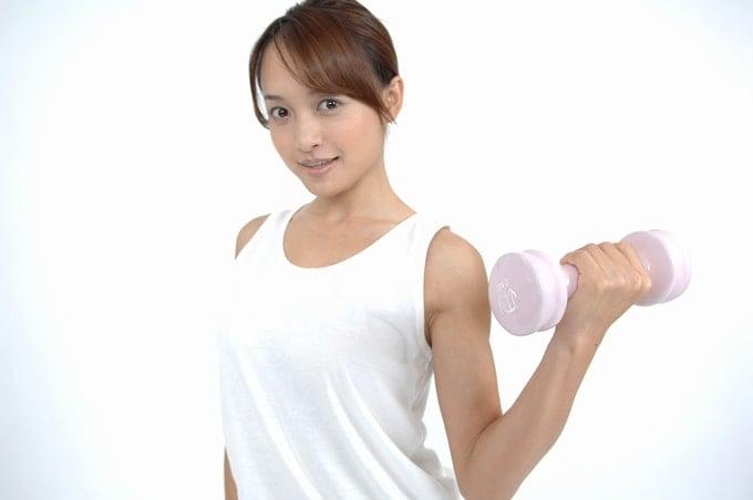 ダンベルトレーニングを行うポニーテールの若い女性。