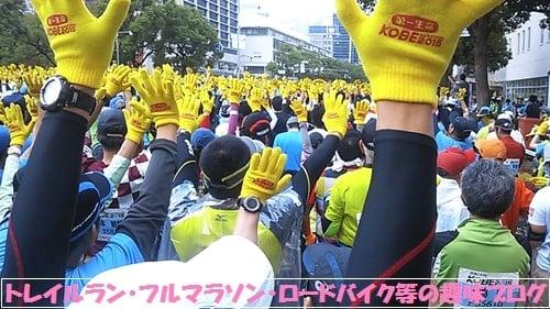 神戸マラソン2015神戸市役所前で黄色い向日葵手袋を空に掲げるランナー達。