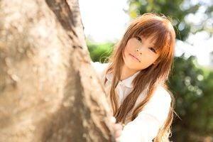 木に触れる若い女