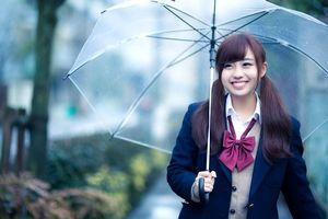 大雨の中、笑顔で傘をさすツインテールの美少女