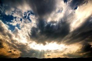 雲が多い夕暮れの空に光が差し込んでいる。