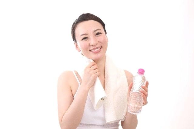 フィットネスで汗をかいた若い女性がタオルとペットボトルを持っている。
