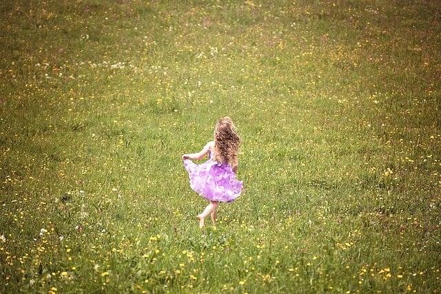 広大な草原を走っている幼い少女。