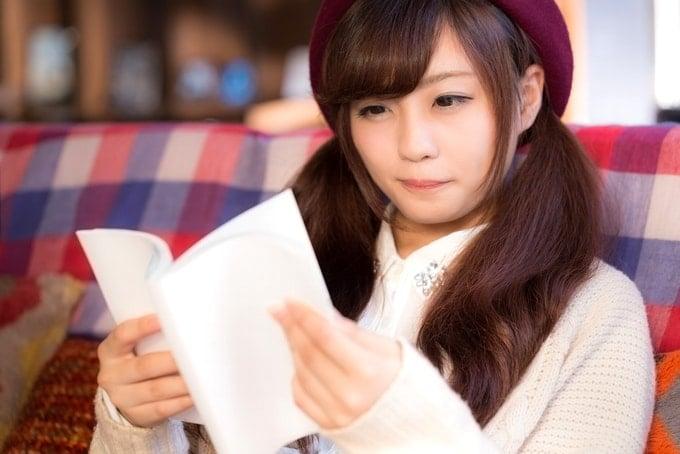 日本山岳耐久レース大会結果記録集を呼んでいる少女。(ハセツネCUP)