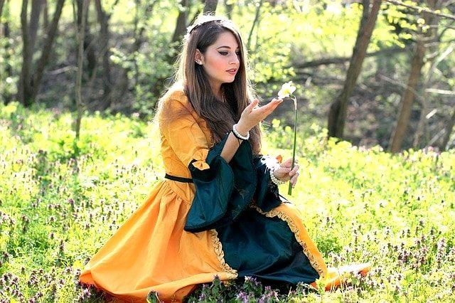 野原でタンポポを持つ美少女。