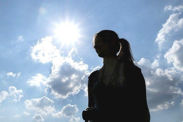 太陽の光を浴びるポニーテールの若い女性。