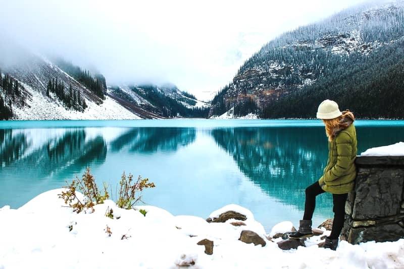 極寒の雪山をダウンコートを着て歩く美女。